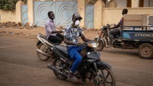 Des burkinabès se couvrent le visage à l'aide d'un masque pour éviter la propagation du virus, à Ouagadougou.