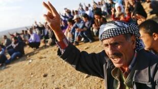 Des Kurdes installés en Turquie regardent les combats dans la ville de Kobane, le 15 octobre 2014.