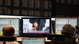 Bourse traders watch TV news about Japan on the trading floor at Frankfurt's stock exchange