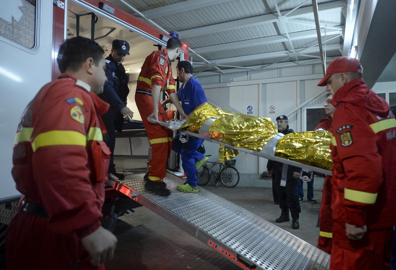 Equipa de socorros evacuando corpos de vítimas à saída da discoteca que pegou fogo em Bucareste este 31 de outubro.