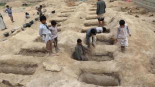 Après un raid de la coalition début août, des enfants inspectent les tombes des morts du bombardement.