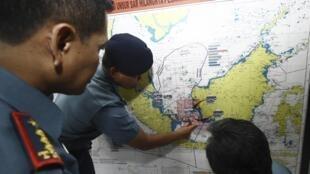 Des militaires indonésiens étudiant une carte de la zone de recherche du vol AirAsia.