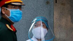 Một nhân viên y tế trong trang bị bảo hộ bên cạnh một quân nhân, tại trung tâm cách ly Bệnh viện Thận Hà Nội trong thời kỳ dịch virus corona. Ảnh chụp ngày 14/04/2020.