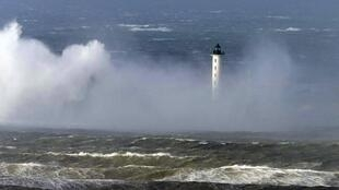 Waves crash against a lighthouse during Storm Christian at Boulogne sur Mer, northern France