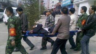 中國甘肅農村信用合作聯社爆炸,援救人員正擡出一名受傷男子 2011年5月13日