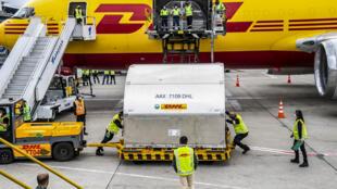 Trabajadores aeroportuarios descargan 117.000 dosis de vacunas contra el covid-19 suministradas a través del mecanismo Covax, en el aeropuerto internacional El Dorado de Bogotá, el 1º de marzo de 2021