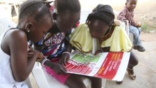 Crianças olham cartaz da campanha contra o vírus Ebola distribuído pela Unicef em Serra Leoa.