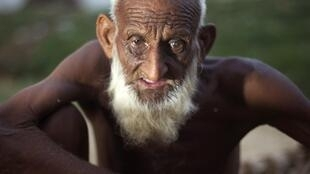 A man who is a flood victim looks on as he rests at a relief camp in Nowshera
