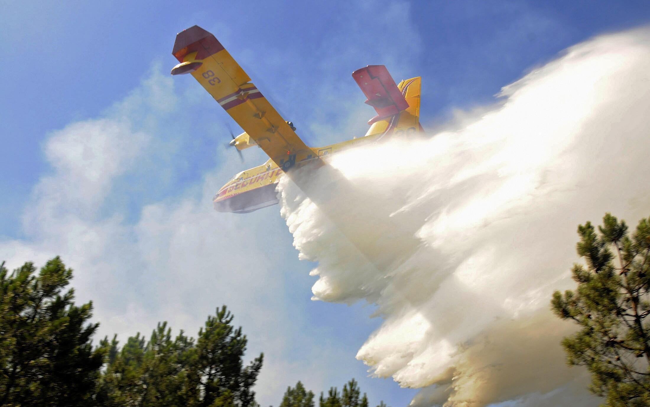 A firefighting plane drops water on the forest fire near Lacanau, western France