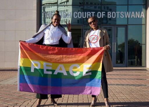 Ativistas posam com uma bandeira arco-íris enquanto comemoram fora do Tribunal Superior de Botsuana, em Gaborone, em 11 de junho de 2019.
