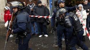 Policiais protegem a área em frente a um posto de polícia no 18° distrito de Paris depois que um homem foi morto a tiros. França, 7 de janeiro de 2016.