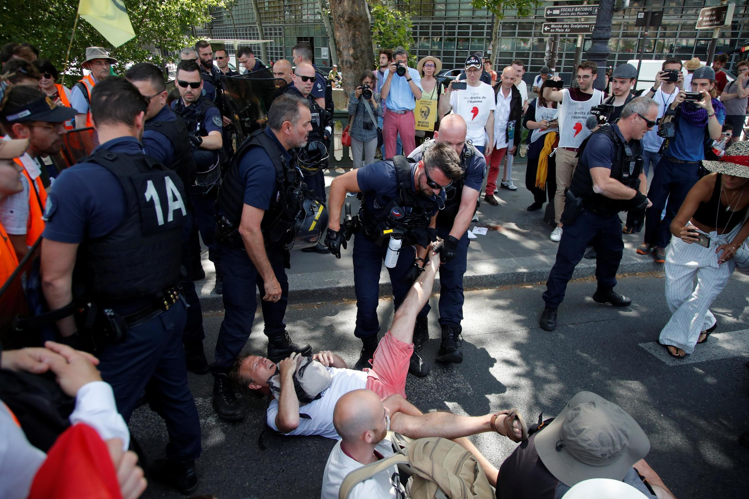 French CRS riot police remove French youth and environmental activists as they block a bridge during a demonstration to urge world leaders to act against climate change, in Paris on June 28.