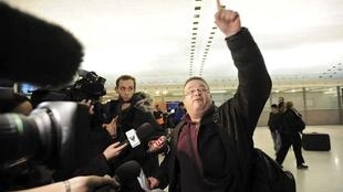 An angry passenger reacts as he speaks with the media in a terminal at Charles de Gaulle airport, near Paris