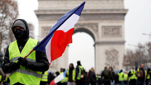 "A protester wearing a yellow vest holds a French flag during a demonstration by the ""yellow vests"" movement in Paris, France, December 15, 2018."