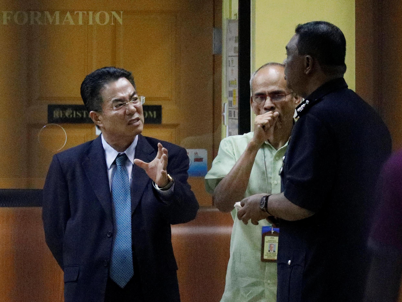 Um alto funcionário da Coreia do Norte na Malásia conversa com policiais diante do IML do Hospital de Kuala Lumpur, onde está o corpo de Kim Jong-nam.