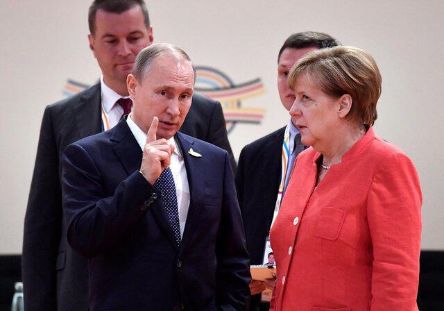 Angela Merkel ergue os olhos para cima de impaciência ao ver o dedo em riste de Vladimir Putin.