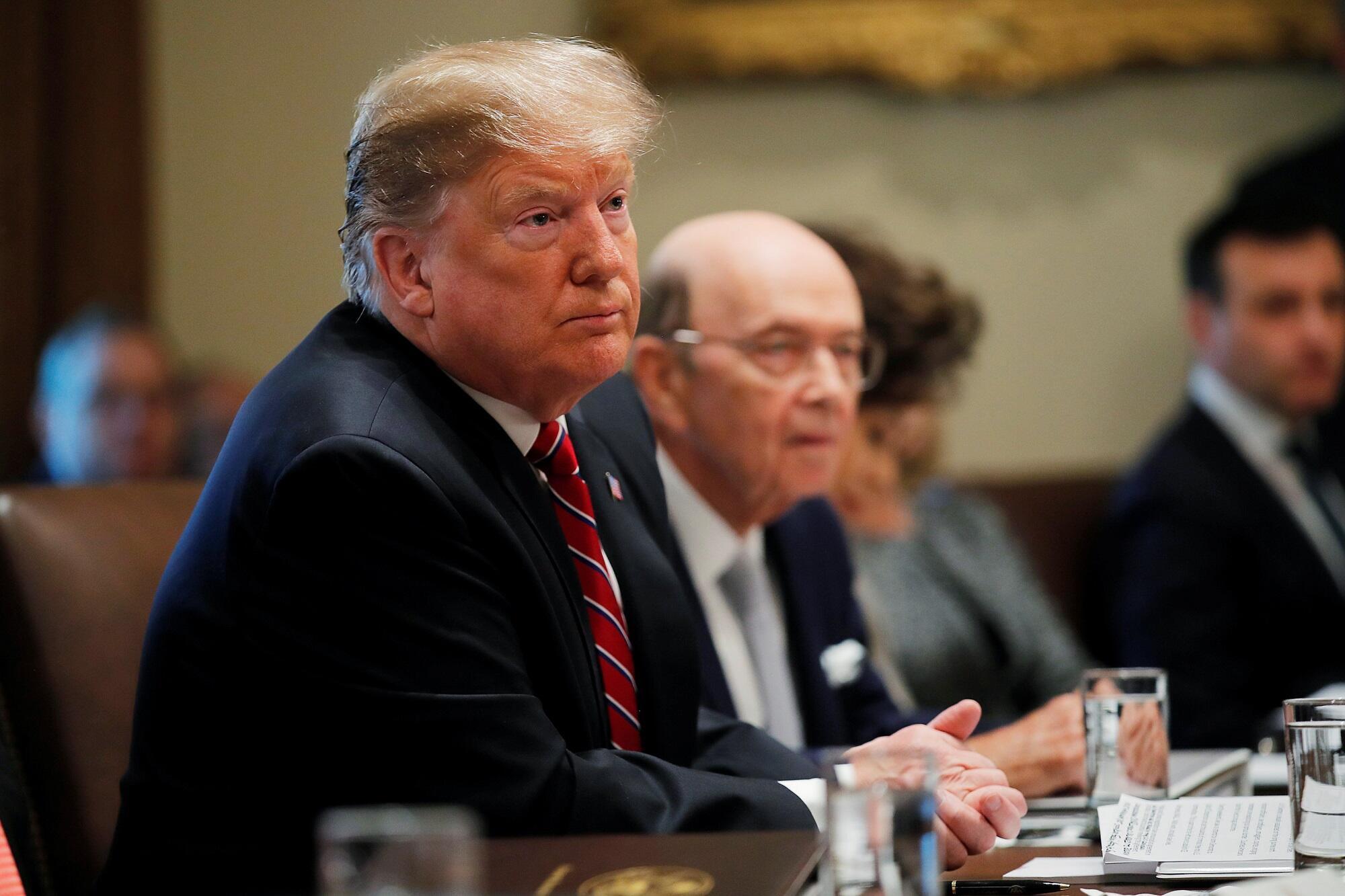 Donald Trump et Wilbur Ross (droite), secrétaire d'État américain au commerce, lors d'une réunion à la Maison Blanche, le 12 février 2019.