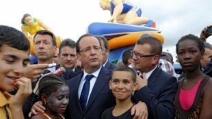 François Hollande entouré de jeunes  à « Clichy Plage»  lors de sa visite à Clichy-sous-Bois, le 31 juillet 2013.