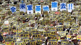 Manifestantes carregam cartazes contra presença militar americana na ilha de Okinawa.