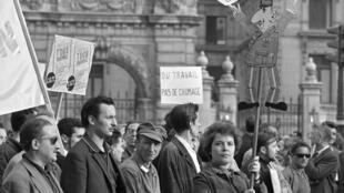 Des manifestants en grève marchent sous une pancarte à l'effigie du président de Gaulle proclamant «La chienlit c'est lui» à Paris le 29 mai 1968, pendant la grève générale de mai 1968, lors du défilé organisé par la CGT.