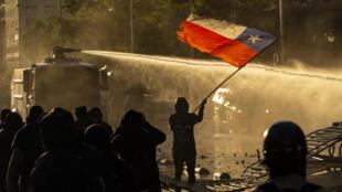 Manifestantes chocan con la policía antidisturbios durante una protesta contra el gobierno del presidente chileno Sebastián Piñera, el 27 de noviembre de 2020 en Santiago