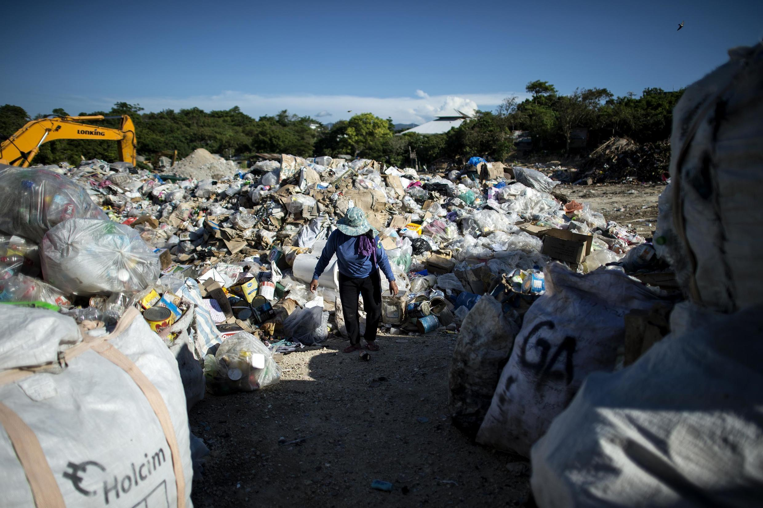 """Gina Galan, 45, collects plastic bottles on the Boracay dumpsite called """"materials recovery facility (MRF)"""" in the Philippine island of Boracay on April 25, 2018."""