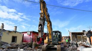 Un bulldozer démolit huit villas construites illégalement, saisies par la police romaine auprès du clan de la mafia de Casamonica, dans le district de Quadraro, sud-est de Rome, le 21 novembre 2018.