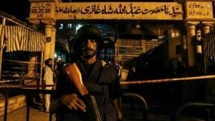 A policeman stands guard outside a Sufi shrine after it was hit by suicide blasts in Karachi