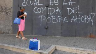 Une femme passe près d'un graffiti dans les rues de Caracas : «Quelle est la nourriture du pauvre désormais ?», le 30 novembre 2018.