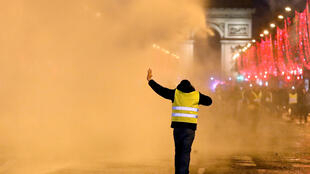 "A protester wearing a yellow vest attends a demonstration by the ""yellow vests"" movement as police use a water cannon on the Champs Elysees near the Arc de Triomphe in Paris, France, December 22, 2018."