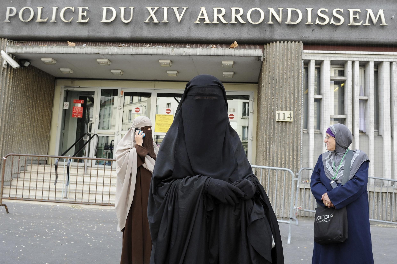 Mulheres de burca em frente a um posto de polícia em Paris