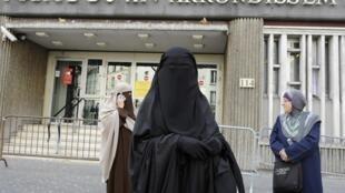 Mulheres de burca em frente a um posto de polícia em Paris.