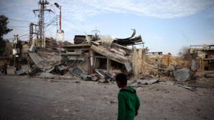 Criança caminha perto de prédios em ruínas na cidade de Duma, em Guta Oriental.