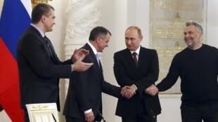 Vladimir Poutine le président russe (2ème D) serrant la main du Premier ministre de Crimée lors de la signature de l'accord d'intégration de la Crimée le 18 mars 2014.