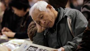 Un vieil homme évacué de la zone de Fukushima, lit son journal dans un gymnase à Kawamata (au nord du Japon), le 14 mars 2011.