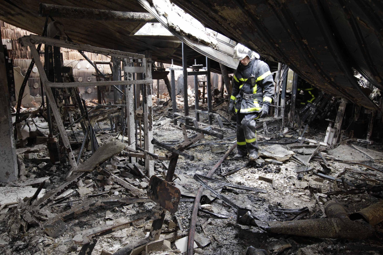 Пожарный осматривает помещение спортзала, сожженное во время столкновений в Амьене 14/08/2012
