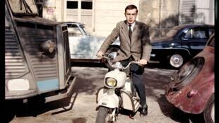 Raymond Depardon,Autoportrait au Rolleiflex (posé sur un mur) 1er scooter de marque Italienne « Rumi », étiquette de presse sur le garde-boue. Ile Saint-Louis. Paris, 1959