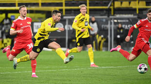 El defensa portugués Raphael Guerreiro chuta para anotar el 2-0 del Borussia Dortmund en el partido liguero contra el FC Union disputado el 21 de abril de 2021 en la ciudad alemana de Dortmund
