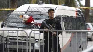 Policial patrulha região do atentado em Túnis em que 12 agentes da guarda presidencial morreram nesta terça-feira (24).
