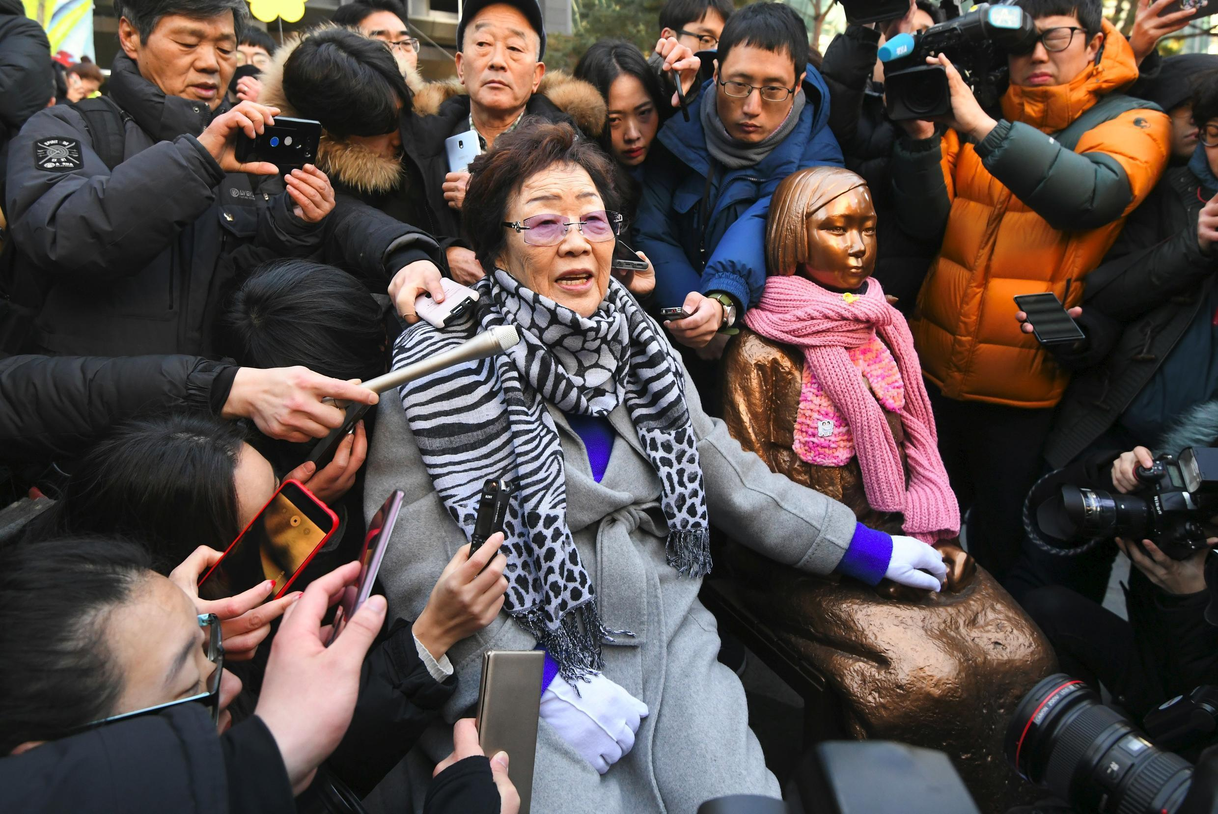 """Former """"comfort woman"""" Lee Yong-Soo (L) stands beside her supporters holding portraits of Chinese, Philippine, South Korean and Taiwanese comfort women who were sex slaves for Japanese soldiers during World War II,"""