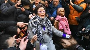"Former ""comfort woman"" Lee Yong-Soo (L) stands beside her supporters holding portraits of Chinese, Philippine, South Korean and Taiwanese comfort women who were sex slaves for Japanese soldiers during World War II,"