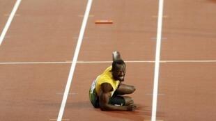 Usain Bolt tumbado en la pista, mira hacia la meta, tras caer lesionado en la final de los 4x100 del mundial de atletismo de Londres 2017.