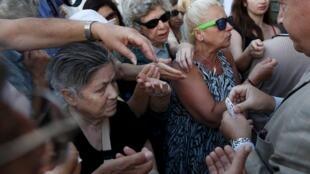 Distribution de tickets prioritaires à des retraités venus retirer de l'argent à la National Bank, à Athènes, ce lundi 13 juillet.