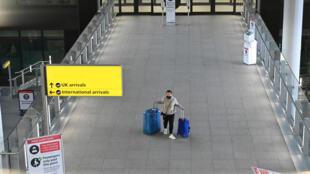 Una pasajera con dos maletas en el aeropuerto de Londres Heathrow, Reino Unido, el 14 de febrero de 2021