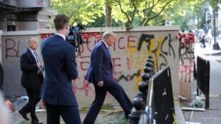 Washington, le 1er juin 2020. Donald Trump passe devant un mur couvert de graffitis récents, pour se rendre à l'église Saint-John après son allocution à la Maison Blanche sur la crise sociale en cours aux États-Unis.