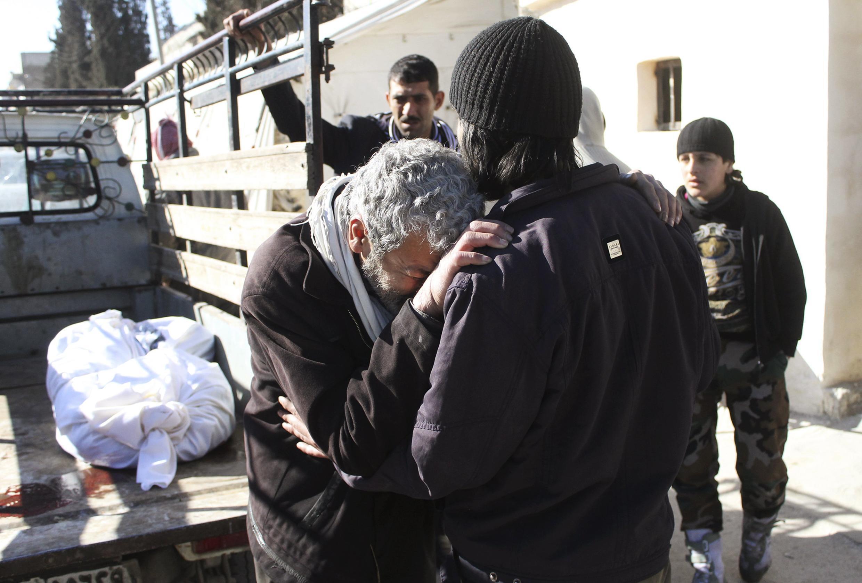 Un homme pleure l'un des ses proches après une attaque aux barils d'explosifs, selon des témoignages d'opposants, le 3 février 2014 à Alep.