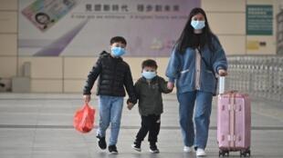 Une famille, portant des masques chirurgicaux, dans un des terminaux passagers menant à Hong Kong, le 8 février 2020.