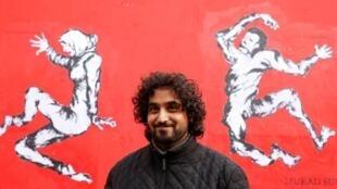 L'artiste yéménite Murad Subay pose devant sa fresque à Paris, le 19 novembre 2019.