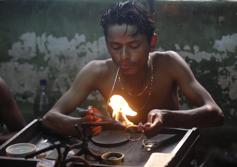 Un jeune orfèvre travaille sur les ornements de bracelets en or dans un atelier de Calcutta, 16 janvier 2013.