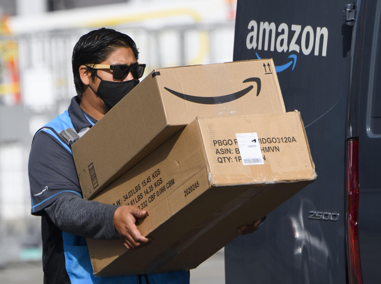 Un repartidor de Amazon carga con dos cajas en un centro de distribución de la plataforma de comercio electrónico, el 2 de febrero de 2021 en Hawthorne (California), al oeste de EEUU